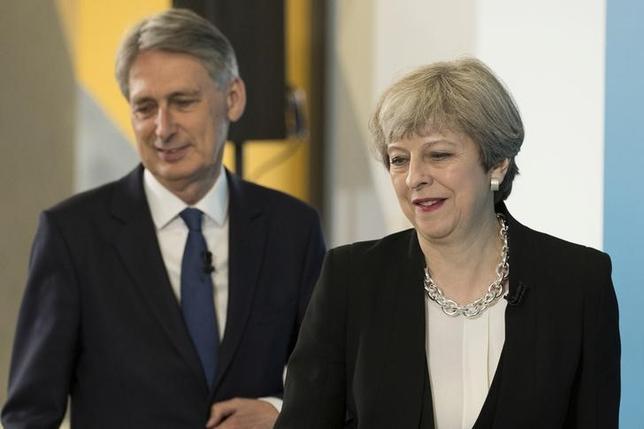 6月13日、英国のハモンド財務相(写真左)は、欧州連合(EU)離脱交渉で英国がEU関税同盟にとどまることを主張する見通し。英紙タイムズが複数の匿名筋の話として伝えた。右はメイ首相、ロンドンで5月代表撮影(2017年 ロイター/Dan Kitwood)