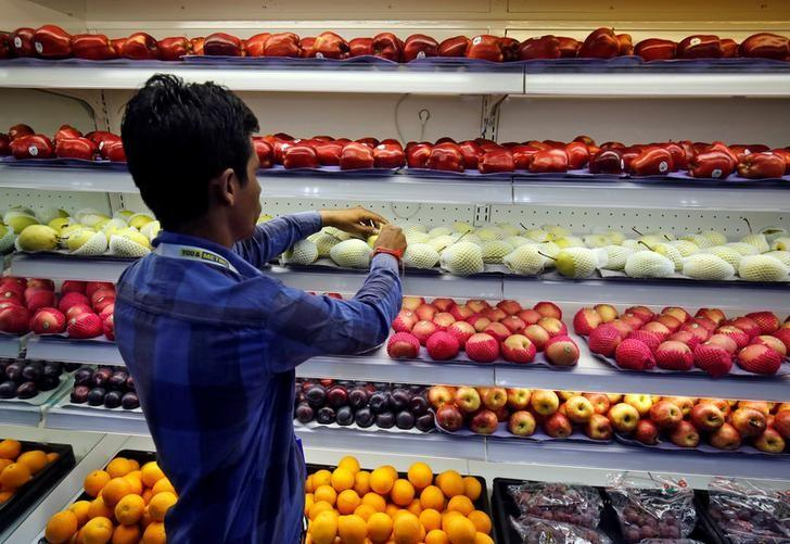 A worker arranges fruits inside a newly opened wholesale store of Metro Cash & Carry India, at Sarkhej on the outskirts of Ahmedabad, India June 13, 2017. REUTERS/Amit Dave