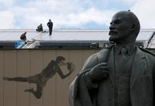 Workers are seen on the roof during the visit of a joint delegation from FIFA and the 2018 FIFA World Cup Russia Local Organising Committee (LOC) to the Luzhniki stadium, which is under reconstruction, as a monument of Soviet state founder Vladimir Lenin is on display in Moscow, Russia, September 7, 2016. REUTERS/Maxim Zmeyev