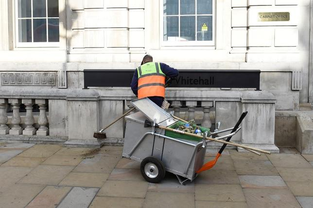 A municipal worker sweeps the street outside the cabinet office in Westminster, central London, Britain, June 9, 2017. REUTERS/Clodagh Kilcoyne