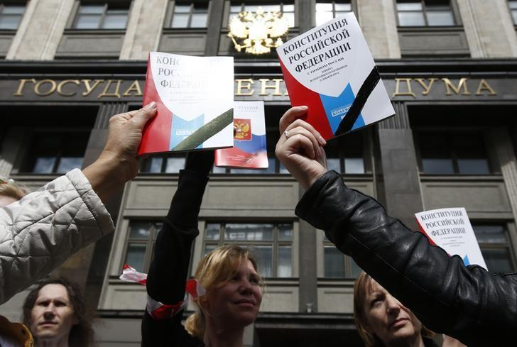 Participants hold booklets containing the Constitution of the Russian Federation during a protest against a housing resettlement program outside the building of the State Duma, the lower house of parliament, in central Moscow, Russia June 14, 2017. REUTERS/Sergei Karpukhin