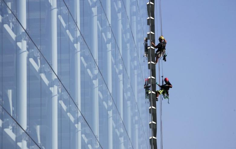 Employees clean the windows of the main building of the European Parliament in Strasbourg, September 21, 2006. REUTERS/Vincent Kessler