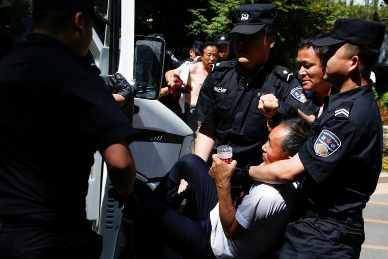Police detain people during a protest denouncing a local authoritiy's decision to reassign their children to an undesired school in Beijing, China June 14, 2017.   REUTERS/Thomas Peter