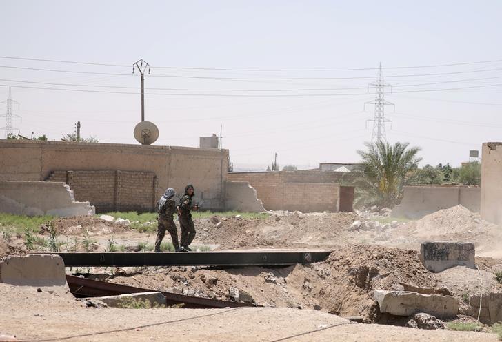 Syrian Democratic Forces (SDF) female fighters cross a bridge in al-Sabahia district, west of Raqqa, Syria June 11, 2017. REUTERS/Rodi Said