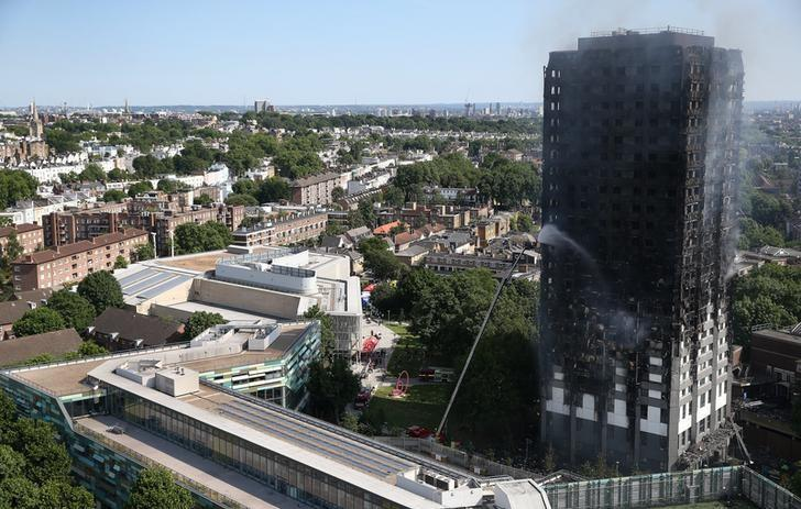 A firefighter directs a jet of water at a tower block severely damaged by a serious fire, in north Kensington, West London, Britain June 14, 2017. REUTERS/Neil Hall
