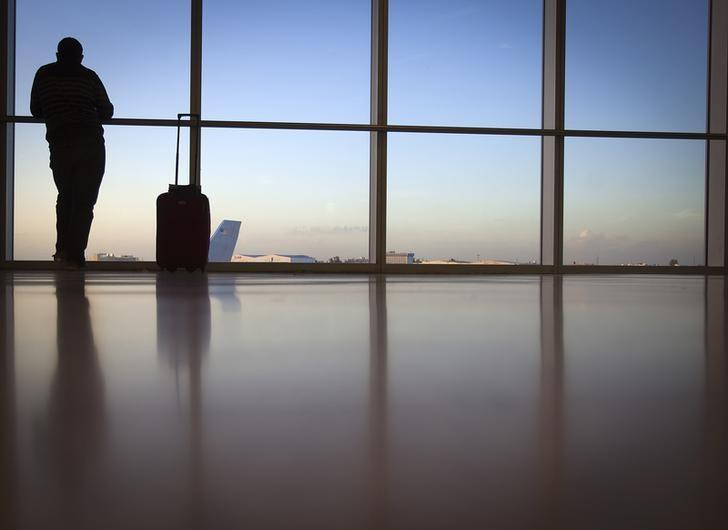 A passenger looks out the window at Miami International Airport in Miami December 10, 2013.    REUTERS/Carlo Allegri