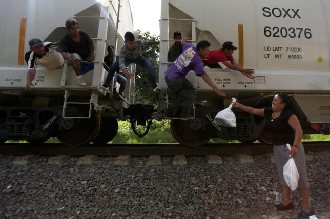 FILE PHOTO - A woman from a group called ''Las Patronas'' (The bosses), a charitable organization that feeds Central American immigrants who travel atop a freight train known as ''La Bestia'', passes food and water to immigrants on their way to the border with the United States, at Amatlan de los Reyes, in Veracruz state, Mexico October 22, 2016. REUTERS/Daniel Becerril/File Photo