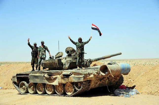 6月15日、シリアの反体制派組織によると、同国南東部の砂漠地帯に展開する米軍の特殊部隊が拠点を拡大している。イランが支援するシリア政権派組織と、米軍が地上で直接対峙するリスクが増しているという。写真は戦車の上でポーズを取るシリア軍兵士たち。13日撮影。SANA提供(2017年 ロイター)