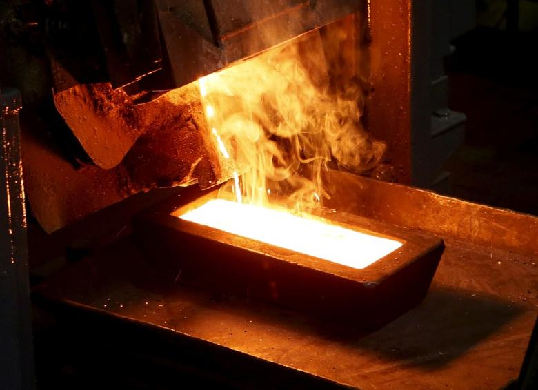 FILE PHOTO: A melter casts an ingot of 92.96 percent pure gold at a procession plant of the Olimpiada gold operation, owned by Polyus Gold International company, in Krasnoyarsk region, Eastern Siberia, Russia, June 30, 2015. REUTERS/Ilya Naymushin/File Photo