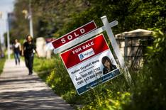 "FILE PHOTO: A woman walks towards a ""for sale"" sign of a home that has been sold in Toronto, Canada, June 29, 2015. REUTERS/Mark Blinch/File Photo"