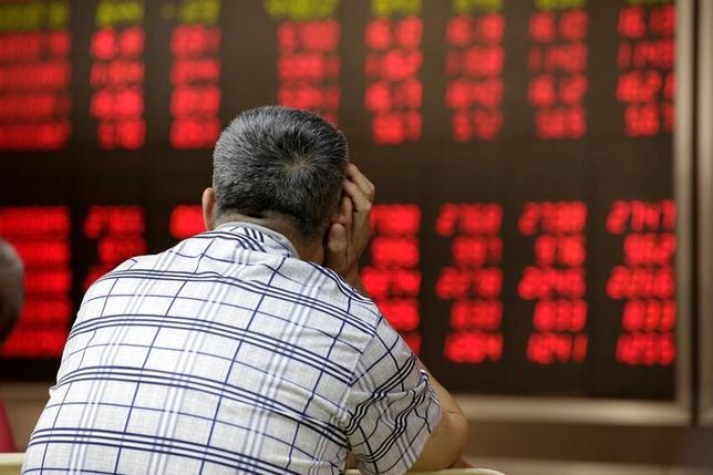 6月14日、株価指数の開発・算出を手掛ける米MSCIは来週、中国本土上場の人民元建て株式(A株)を新興国株指数に組み入れるかどうかを発表する。写真は、証券会社の株価ボードを眺める投資家。北京で昨年6月撮影(2017年 ロイター/Jason Lee)