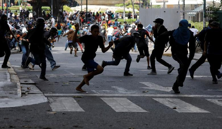 Demonstrators run from security forces during a rally against Venezuela's President Nicolas Maduro's government in Caracas, Venezuela June 14, 2017. REUTERS/Carlos Garcia Rawlins