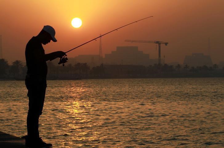 2017年6月15日,卡塔尔多哈,一名男子在水边钓鱼。REUTERS/Naseem Zeitoon