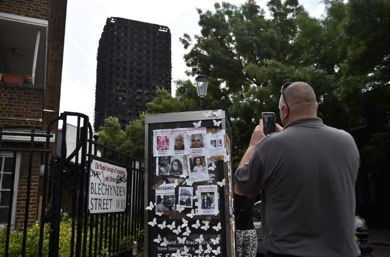 A man photographs missing persons posters near the scene of the fire that destroyed the Grenfell Tower block (IN BACKGROUND), in north Kensington, West London, Britain June 16, 2017. REUTERS/Hannah McKay