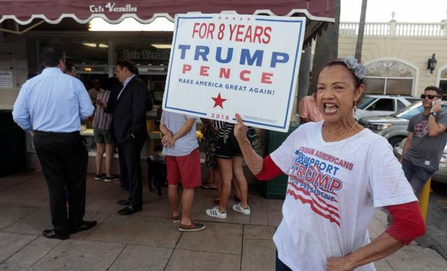 Madelyn del Rio, from Dominican Republic, holds a sign up in front of the Cuban popular Cafe Versailles in the Little Havana district as U.S. President Donald Trump is expected to announce changes to U.S.-Cuba policy, in Miami, Florida, U.S. June 16, 2017.REUTERS/Javier Galeano