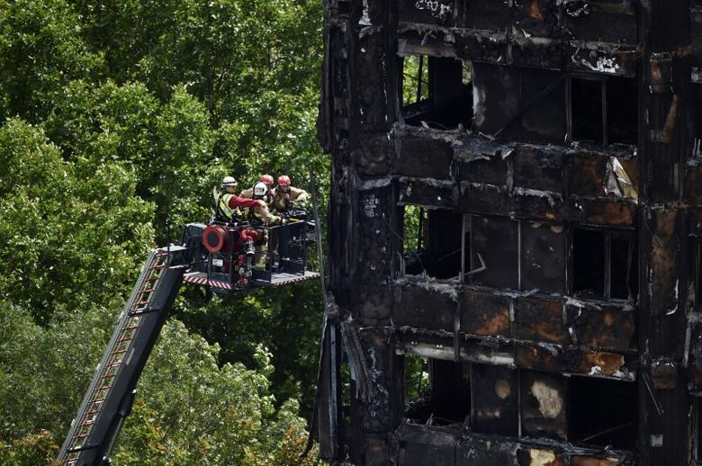 Firefighters at the Grenfell Tower block which was destroyed in a disastrous fire. REUTERS/Hannah McKay