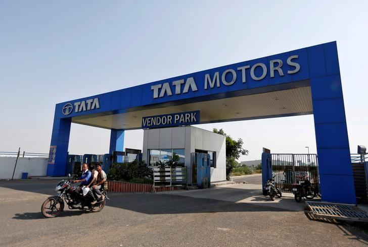 FILE PHOTO: Men ride a motorbike past a Tata Motors car plant at Sanand, in Gujarat, India October 27, 2016. REUTERS/Amit Dave/File photo