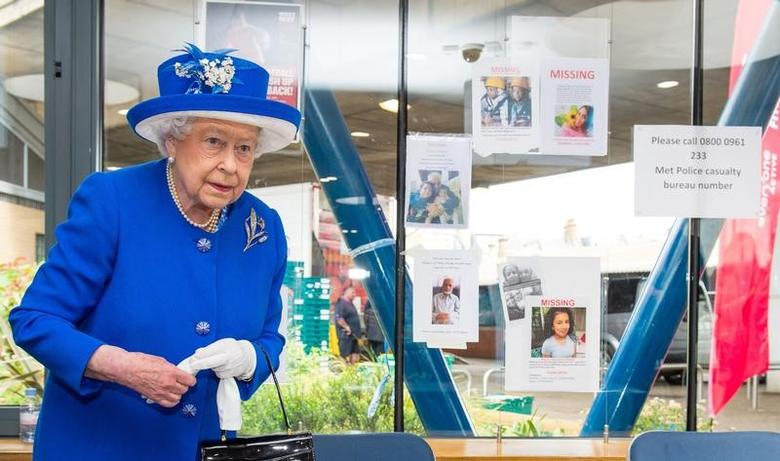 Britain's Queen Elizabeth walks past missing person posters during a visit to the Westway Sports Centre following the fire at the Grenfell Tower block, in north Kensington, West London, Britain June 16, 2017.  REUTERS/Dominic Lipinski/Pool
