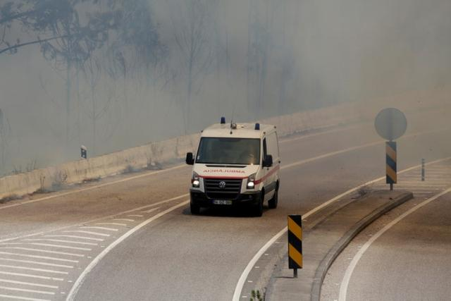 An ambulance makes its way through the IC8 motorway during a forest fire near Pedrogao Grande, in central Portugal, June 18, 2017.  REUTERS/Miguel Vidal
