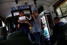 """Una tarde de principios de mayo, Claudia Lizardo, una directora creativa de 29 años, regresaba, junto a unos amigos, a su casa en Caracas tras una de las tantas protestas contra el Gobierno de Nicolás Maduro que se han sucedido en los últimos dos meses.  Imagen de un grupo de artistas actuando en un autobús público de Caracas, el 10 de junio de 2017. Sobre el marco de cartón que representa una televisión se puede lever """"El Bus TV"""". REUTERS/Iván Alvarado"""