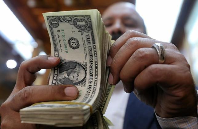 6月18日、7日付の米投資情報週刊紙バロンズは、米銀行株について、このところのハイテク株の売りが追い風となっており、今年後半に大幅上昇する可能性があるとの見方を示した。写真はドル紙幣を数える男性、カイロで3月撮影(2017年 ロイター/Mohamed Abd El Ghany)