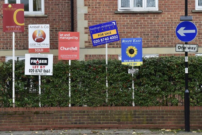 Property sale and rental signs are seen next to a street sign in London, October 18, 2014.  REUTERS/Toby Melville