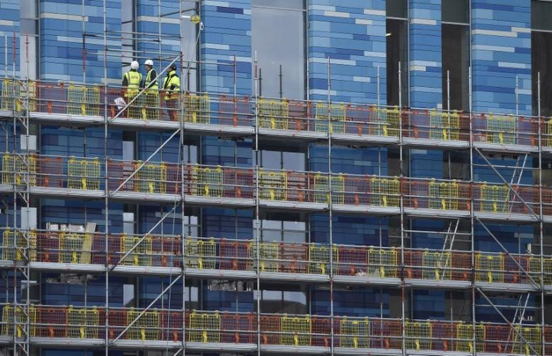 FILE PHOTO: Workers stand on scaffolding on a new building at Battersea in London, Britain, March 7, 2016.  REUTERS/Toby Melville/File Photo