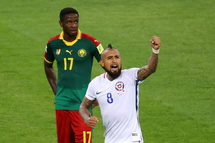 Soccer Football - Cameroon v Chile - FIFA Confederations Cup Russia 2017 - Group B - Spartak Stadium, Moscow, Russia - June 18, 2017   Chile's Arturo Vidal celebrates scoring their first goal as Cameroon's Arnaud Sutchuin Djum looks dejected    REUTERS/Kai Pfaffenbach