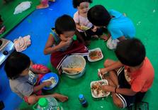 Children, who left their homes with their families to avoid the intense fighting between government forces and insurgents from the Maute group, eat their meals inside the evacuation centre in Baloi Village, Lanao Del Norte, Philippines June 19, 2017. REUTERS/Romeo Ranoco