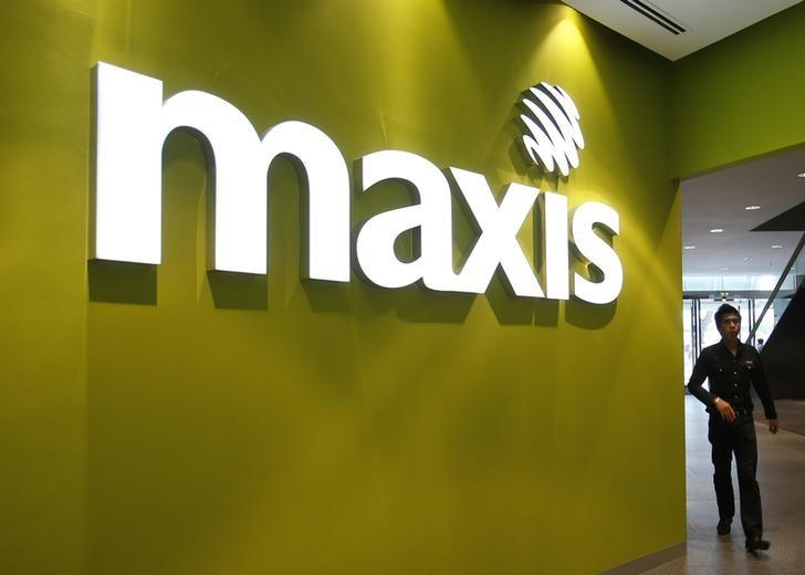 A customer walks past a logo of Malaysia's mobile network operator Maxis at its headquarters in Kuala Lumpur September 3, 2013. REUTERS/Bazuki Muhammad