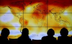 La Unión Europea dijo el lunes que estaba profundizando sus alianzas con otros firmantes del acuerdo sobre el clima de París para asegurar su implementación, rechazando las demandas del presidente estadounidense, Donald Trump, para renegociar el pacto. En la imagen de archivo, siluetas de personas mirando una pantalla  con un mapa mundial en una conferencia sobre el clima en Le Bourget, cerca de Paris.  REUTERS/Stephane Mahe/File Photo