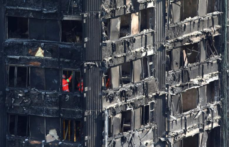 Members of the emergency services work inside burnt out remains of the Grenfell apartment tower in North Kensington, London, Britain, June 18, 2017. REUTERS/Neil Hall