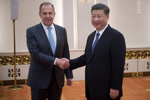 China's President Xi Jinping (R) shakes hands with Russia's Foreign Minister Sergey Lavrov (L) as he meets with foreign affairs officials from the BRICS countries at the Great Hall of the People's Fujian Room in Beijing on June 19, 2017. REUTERS/Nicolas Asfouri/Pool