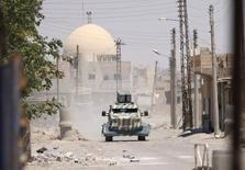 سيارة عسكرية تابعة لقوات سوريا الديمقراطية في غرب الرقة يوم الأحد. تصوير: رودي سعيد - رويترز.