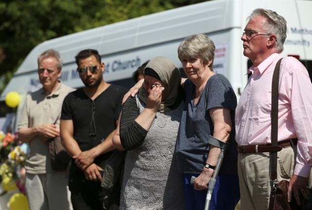 People attend a minute's silence for the victims of the Grenfell Tower fire near the site of the blaze in North Kensington, London, Britain, June 19, 2017. REUTERS/Marko Djurica