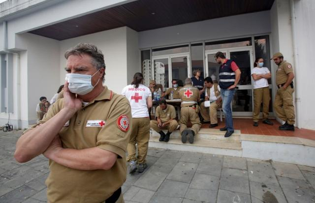 Red Cross and other relief personnel are seen outside a relief centre for people affected by a forest fire in Figueiro dos Vinhos, Portugal, June 19, 2017. REUTERS/Miguel Vidal
