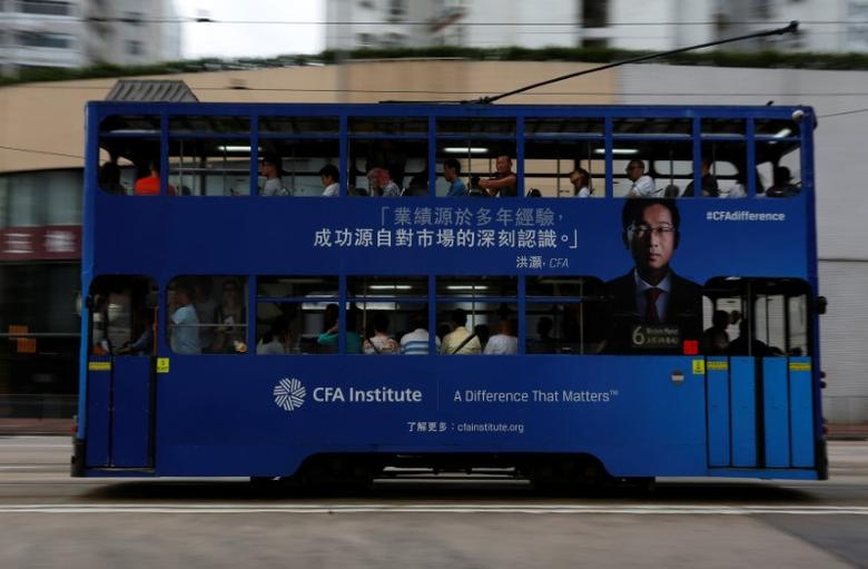 A tram with an advertisement of CFA Institute, featuring Hao Hong, head of research at Bocom International, drives past in Hong Kong, China October 6, 2016. Picture taken October 6, 2016.  REUTERS/Bobby Yip