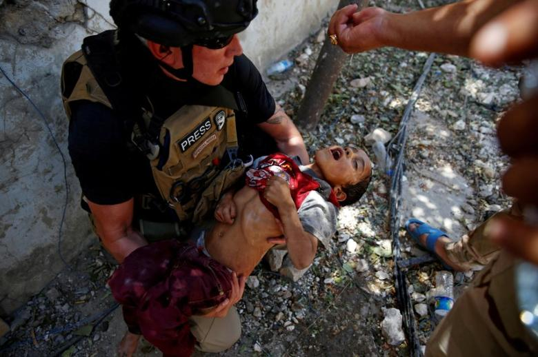 An Iraqi soldier from the 9th Armoured Division gives drops of water to a dehydrated child rescued earlier by soldiers at the frontline, during the ongoing fighting between Iraqi forces and Islamic State militants near the Old City in western Mosul, Iraq, June 13, 2017. REUTERS/Erik De Castro