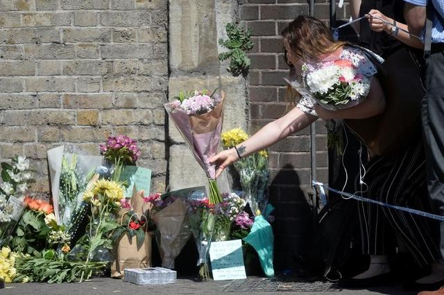 A woman leaves flowers near the scene of an attack where a van was driven at Muslims outside a mosque in Finsbury Park in North London, Britain, June 19, 2017. REUTERS/Hannah McKay