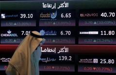 رجل يمر أمام لوحة إلكترونية تعرض أسعار أسهم في البورصة السعودية بالرياض - صورة من ارشيف رويترز.