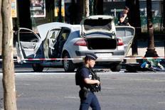 أحد أفراد الشرطة الفرنسية قرب سيارة محترقة في موقع هجوم في باريس يوم الاثنين. تصوير: شارل بلاتيو - رويترز.