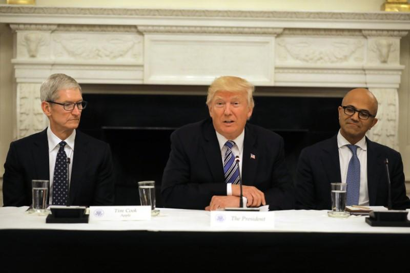U.S. President Donald Trump participates in an American Technology Council roundtable, accompanied by Tim Cook, CEO of Apple (L) and Satya Nadella CEO of ...