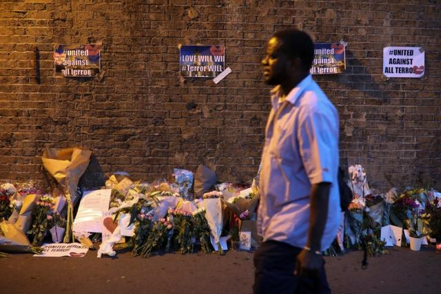 A man walks past messages and tributes left near to where a van was driven at Muslims in Finsbury Park, North London, Britain, June 19, 2017. REUTERS/Marko Djurica
