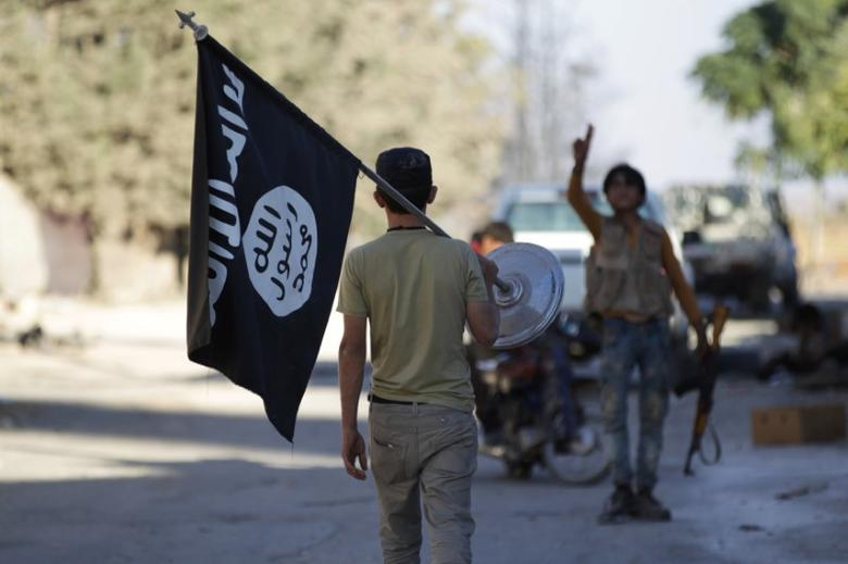 FILE PHOTO - A rebel fighter takes away a flag that belonged to Islamic State militants in Akhtarin village, after rebel fighters advanced in the area, in northern Aleppo Governorate, Syria, October 7, 2016. REUTERS/Khalil Ashawi