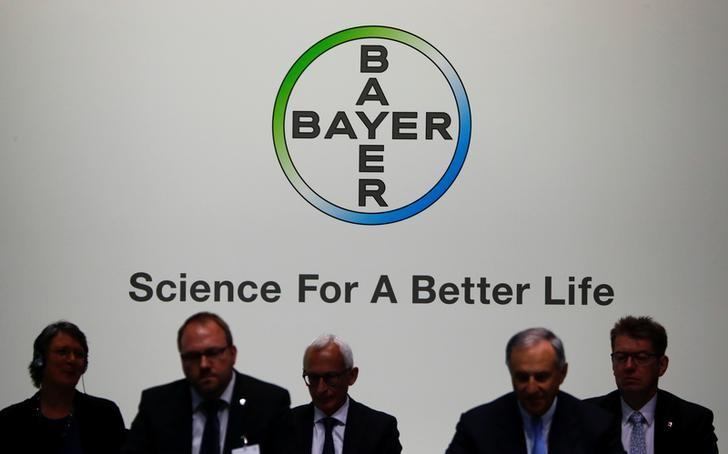 Members of the supervisory board of German pharmaceutical and chemical maker Bayer AG are silhouetted against the company's logo at the annual general shareholders meeting in Bonn, Germany, April 28, 2017.      REUTERS/Wolfgang Rattay