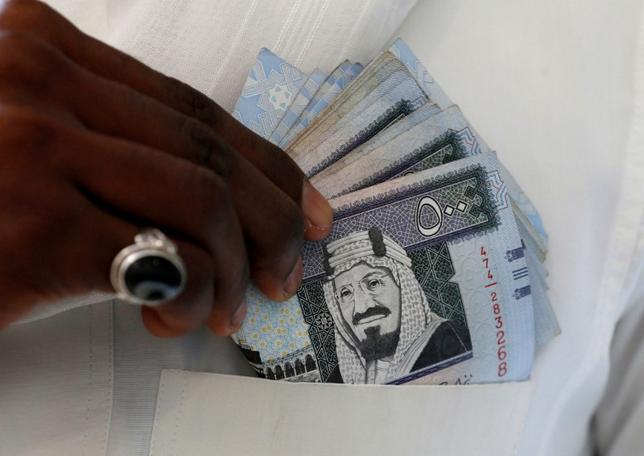 6月21日、株価指数の開発・算出を手掛ける米MSCIは、サウジアラビア株式の新興国株指数組み入れを検討し、2018年6月に結論を発表すると明らかにした。写真はサウジの通貨リヤル紙幣。リヤドで昨年1月撮影(2017年 ロイター/Faisal Al Nasser)