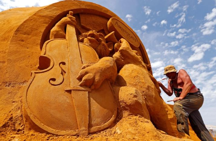 Sand carver Sergey Aseer from Russia works on a sculpture during the Sand Sculpture Festival 'Disney Sand Magic' in Ostend, Belgium June 22, 2017. Yves Herman