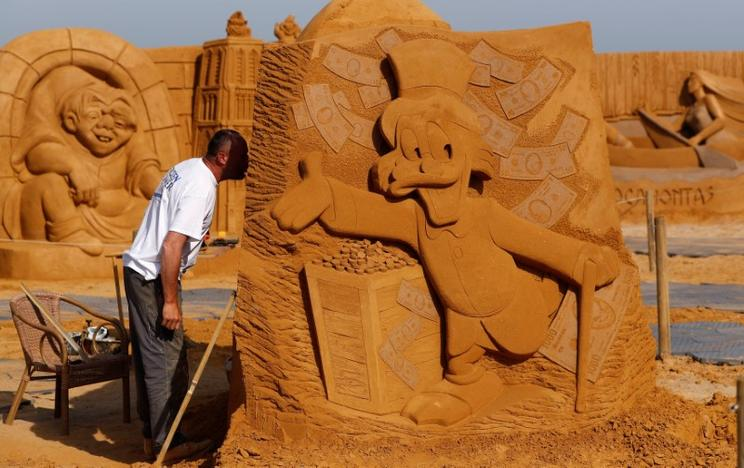 Sand carver Teimur Ilya Shanin from Russia works on a sculpture during the Sand Sculpture Festival 'Disney Sand Magic' in Ostend, Belgium June 22, 2017. Yves Herman