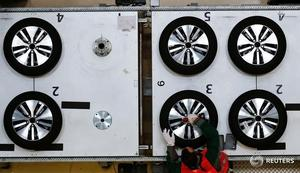 Worker assembles tyres for a VW e-Golf electric car in Dresden