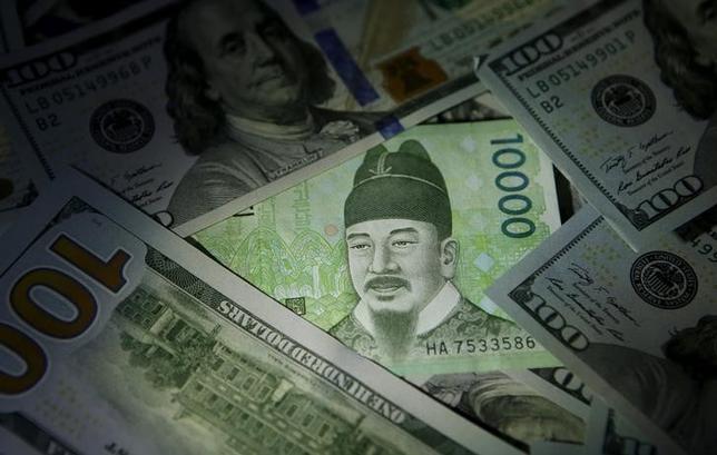 6月26日、アジア市場で債券需要が8カ月ぶりの高水準となっている。写真は韓国ウォン紙幣と米ドル紙幣。ソウルで2015年12月撮影(2017年 ロイター/Kim Hong-Ji)